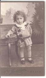 Sønnen Anker f. 1909 er fotograferet i 1911 af F.P. Therkildsen, Beder, i sit fi ne tøj - kort kjole med blonder i halsen, korte bukser, lange strømper og sko med rem om anklen.