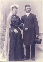 Bryllupsbillede 1903 Jakob og Kirsten Kristensen. Bruden er i sort med handsker, høj hals, snæver talje og vidde i kjolen. Jakob er i lang frakke, høj hat og hvid kravat i halsen.