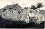 To teglværksarbejdere i gang med at læsse sten på trillebør. Huset Bækvej 2 ses i baggrunden
