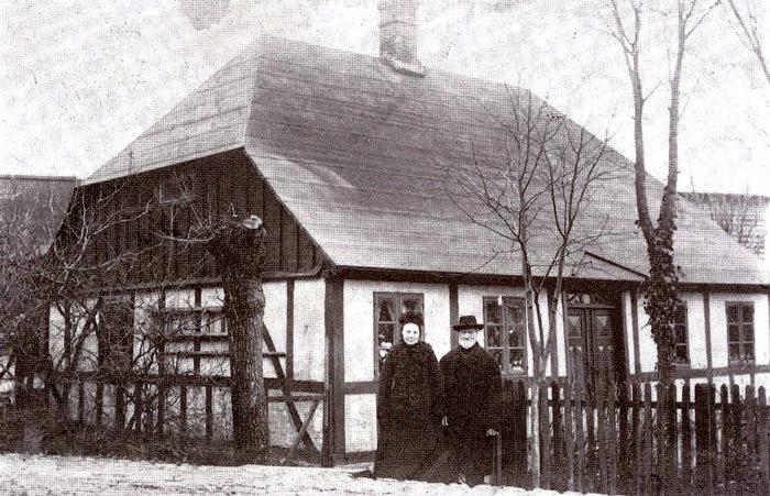 """Bredgade 57, Malling. Huset blev i 1869 købt af Christian Jensen, også kaldt """"Malling Christian"""". Her startede i 1874 den første brugs i Malling. Butikken var indrettet i en stue. 1 1935, da Inger Marie og Christen Nielsen købte huset, fandtes endnu et kampestensrum under stuegulvet. Her var brugsens ølkælder. På billedet ses den første uddeler, Christian Jensen og hustruen Marie."""