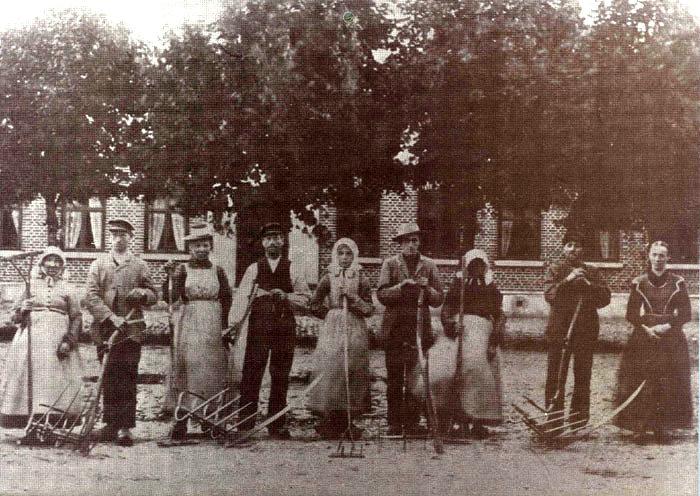 """""""Bundgaard"""" Fløjslrup, omk. 1908. Høstfolkene er parat til at gå i marken for at høste. En karl og en pige gik sammen. Karlen høstede med Ieen, hvorpå mejekrogen var monteret, således at stråene blev samlet pænt. Af stráene lavede pigen neg af passende størrelse med kratten, en rive helt af træ med 4 lange tænder. Så tog hun en håndfuld strå i hver hånd, bandt dem sammen med en særlig knude til et langt bånd, som så blev bundet omkring neget. Negene blev så sat i traver. Fra venstre står Bertha Marie ? , Peder Jacobsen, Katrine ? , Jørgen Pedersen (senere gift med Katrine), Maren Jacobsen, Jaoob Jacobsen, Ane ? , Niels Mikkelsen, enke pá """"Bundgaard"""" Rasmine Jacobsen."""