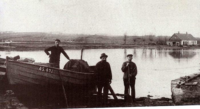 """Norsminde havn omkring 1920. Her hørte nogle få fiskerbåde hjemme. Båden, der her er trukket på land, ejes af Emil Olsen, som står i båden. De to andre er ukendte. I baggrunden ses """"Fisker Mines hus"""" (Vilhelmine Pedersen)."""