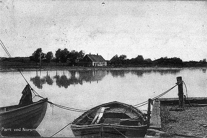 """Et skønt billede taget fra havnen i Norsminde omkring århundredskiftet. Som det kan ses ligger """"Fisker Mines"""" hus ret så enligt langs landevejen. Huset har været fredet i mange år og ejet af Skov- Og Naturstyrelsen. som solgte det for nogle år siden til Frank Hjorth"""