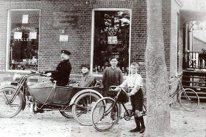 Cykelhandler Hans Christian Hermansen med familien uden for forretningen, Bredgade 66 i Malling. H. C. Hermansen sidder på motorcyklen med sin kone i sidevognen. Stående er det sønnerne Harald og Henry med cyklen. Billedet er fra omkring 1915.