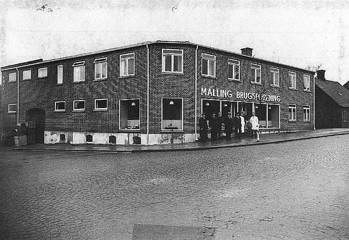 """Et billede fra november 1939 da Malling Brugsforening havde gennemført en større ombygning på ejendommen, der er fra 1889. Bl. a. blev der bygget i højden, så der blev en lejlighed til uddeleren. Bestyrelse og uddelerpar er her fotograferet foran den """"nye"""" Brugs. Fra v.: Marinus Fjeldbo, Frederik Christensen, Jens Mortensen, Hans Sonnichsen. Niels Elmose, Anna Larsen, Niels Andersen, Jens Larsen (søn af uddeleren) og uddeler Thomas Larsen. I juni 1999 er det 125 år siden """"Malling Forbrugsforening"""" blev oprettet."""