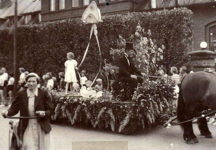 """I begyndelsen af 1950'erne blev der i forbindelse med Malling Gymnastikforenings Sportsfest gennemført optog. Her er en flot pyntet hestevogn, hvor man illustrerer eventyret """"Tommelise"""". De andre hestevogne illustrerede andre eventyr. Der var så afstemning om den bedste udsmykning, som blev præmieret. Optoget havde et orkester foran. Billedet her er fra 1953."""