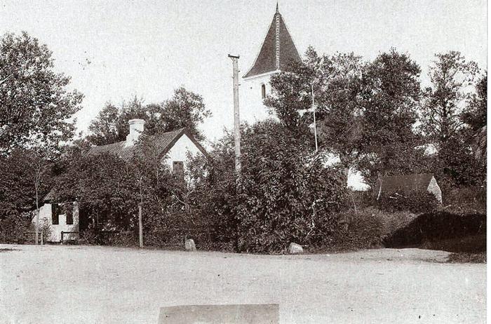 Malling Kirke med det lille, hvide hus., som hørte til kirken. Her boede skolelæreren og senere ringeren og graveren, og det er sandsynligvis Mallings første skole. Til højre ses hjørnet af Stenhøjgård, der blev flyttet til Tværgade i 1903. Det lille kampestenshus var Mallings sprøjtehus.