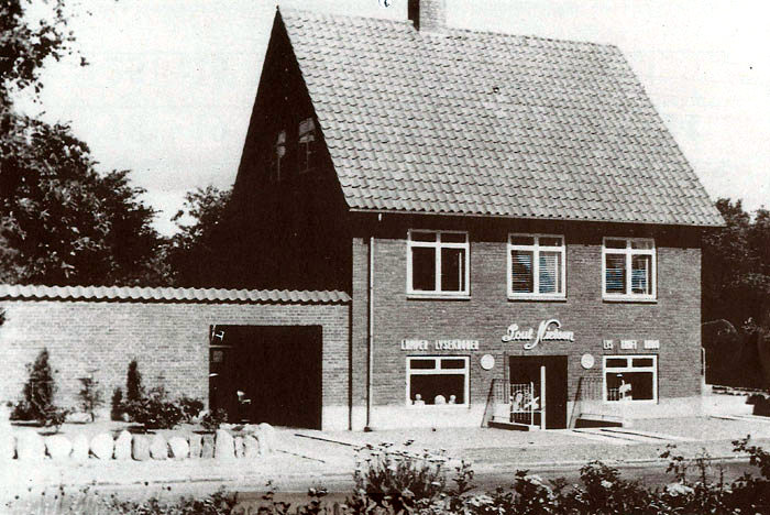 Malling Kirkevej 5. Huset er opført i 1949-50 af el-installatør Poul Nielsen. Som man kan se, var der butik i kælderen. Aase og Carsten Ølholm overtog forretningen d. 1. november 1967, da de var kommet hjem fra Grønland. Siden er huset og forretningen udvidet adskillige gange, så det har været nødvendigt at købe ekstra jord.