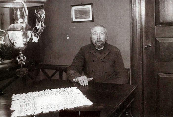 """Anders Sørensen, bedre kendt som """"Goliat"""", er fotograferet i """"Dalsgaard"""" i Langballe i 1918. Goliat, der oprindelig var fra Mors og havde været sømand, fortalte selv, at han var forlist på vej fra Århus, og på den måde var han havnet i Fulden, hvor han boede til sin død i februar 1938. Han ernærede sig ved handel med fisk og tilfældigt arbejde rundt i sognet. Han var kendt overalt på egnen både for sit ejegode og barnlige væsen og for sin svage karakter. Huset i Fulden havde han købt af Jens Rasmussen for en pot brændevin om dagen, så længe Jens levede."""