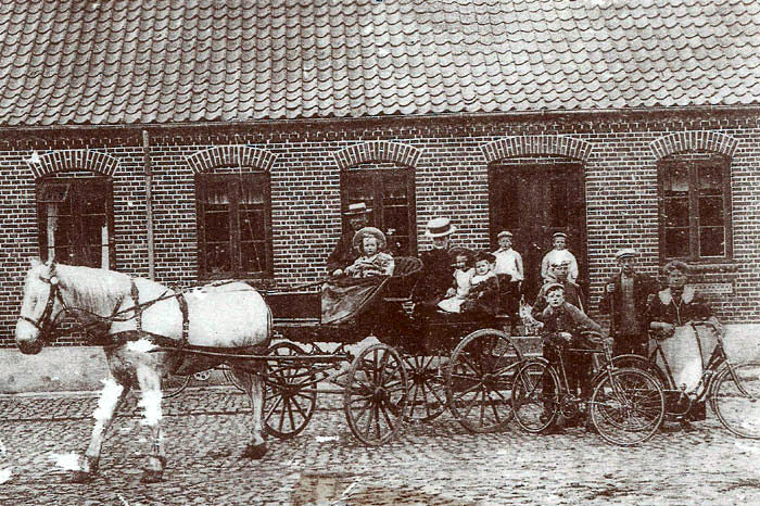 """""""Fulden Møllegaard'"""" s stuehus først i 1900-tallet. På den flot stenpikkede gårdsplads holder formodentlig ejeren Peder Pedersen med hustru og børn i gårdens fladbundede fjedervogn parat til en køretur. Når man dengang blev fotograferet skulle alle gårdens folk være med. """"Fulden Møllegaard"""" har været fæstegård under Vilhelmsborg og blev i 1875 flyttet til sin nuværende plads i Fulden by. Gården har matr. nr. 6a Fulden. Desværre er billedet lidt skadet."""