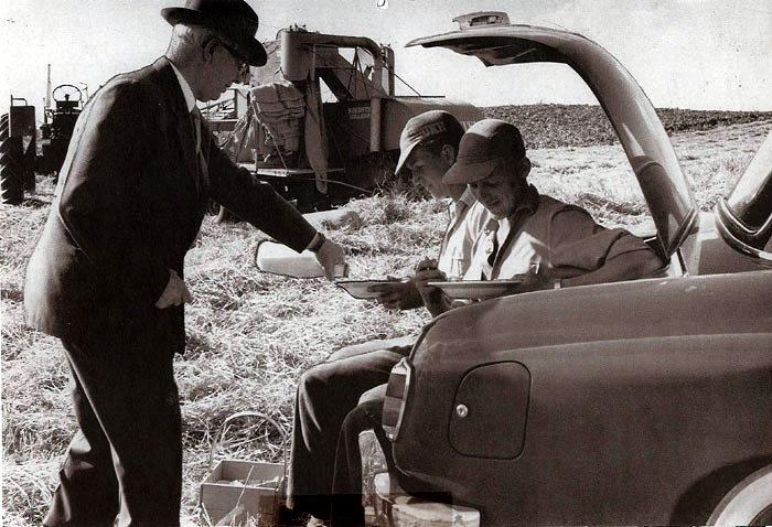 Høsten er i fuld gang på Malling Landbrugsskole i 1958. Forstander Søren Larsen-Sørensen er i marken for at give eleverne en forfriskning. Mejetærskeren var ikke selvkørende men blev trukket af en traktor, og kornet kom ikke i tank men i sække.