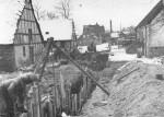 """Opgravning af kloak til Malling skole, der blev taget i brug august 1959. Billedet her er fra d. 14. dec. 1957, og med den seneste kloakering i erindring må dette kaldes primitivt, men det fungerede. Gennembrydningen foregår ved """"Lundshøj gård"""", hvor stuehuset til højre nu er præstebolig, mens der er P-plads, hvor udbygningerne lå. Vejen er nu forbindelsesvej mellem Kirkevej og Lundshøjgårdsvej."""