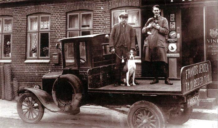 Frands Jensens købmandsbutik og butikkens Iadbil i Beder på hjørnet af Byagervej og Beder landevej ca. 1920.-30. Kæledyrene katten og hunden er kommet med. Bemærk telefonnummeret på bagsmækken: Nr. 11! Bygningen er nedrevet.