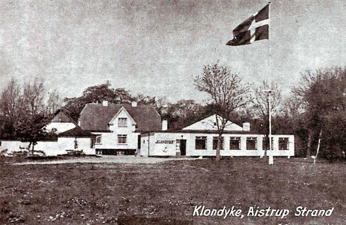 """Ved Ajstrup Strand på Strandbovej lå restauranten Klondyke fra slutningen af l930erne. Den skiftede senere navn til Solvigen og Kystkroen. Bygningen blev revet ned i 1992, og der blev bygget sommerhuse på grunden. Bag på dette postkort står """"Klondyke-Valsen"""": Her kysser Kattegats blånende vand - Jydernes snehvide Strand. . .. Det gik vist lystigt for sig på Klondyke."""