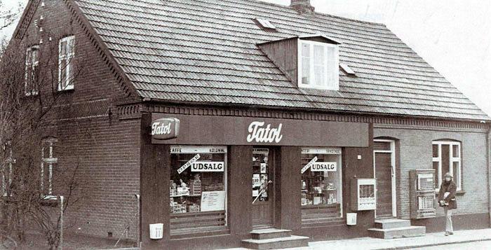 """Forretningen Tatol på Ajstrupvej 22, Malling holder ophørsudsalg i 1970. Pigen på billedet er Lena Melchior Jensen, nu bosat i Canada. Forretningen ejes i 1970 af Ellen A. Rasmussen også kaldet Ginge. Før """"Tatol"""" hed forretningen """"Tusindhandlen"""" og solgte da også vidt forskellige ting: Tapet, farver, legetøj, isenkram, cigaretter, chokolade mv. Forretningen åbnede ca. 1920."""