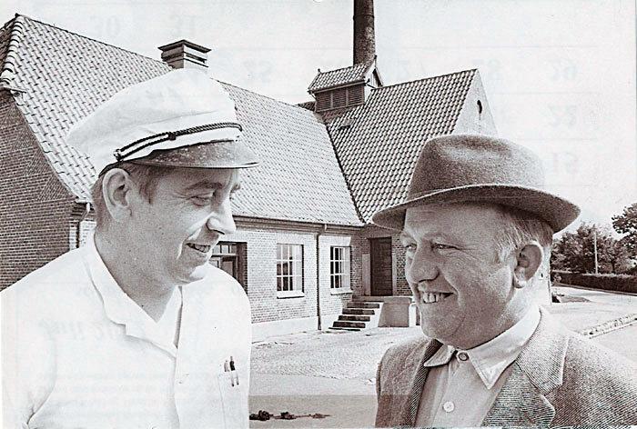 Beder Andelsmejeri, Kirkebakken 5, den 5. august 1961. Mejeribestyrer Ernst Rasmussen til venstre og formanden for andelsmejeriet gårdejer Otto Chr. Bay, Langballe. Mejeriet blev taget i brug i 1930 og lukket i 1969. Bygningen indrettes herefter til industri og fra 1991 til posthus, kontorer, fysioterapi mv. Det første mejeri i Beder lå på Byvej 17 (1885-1930).