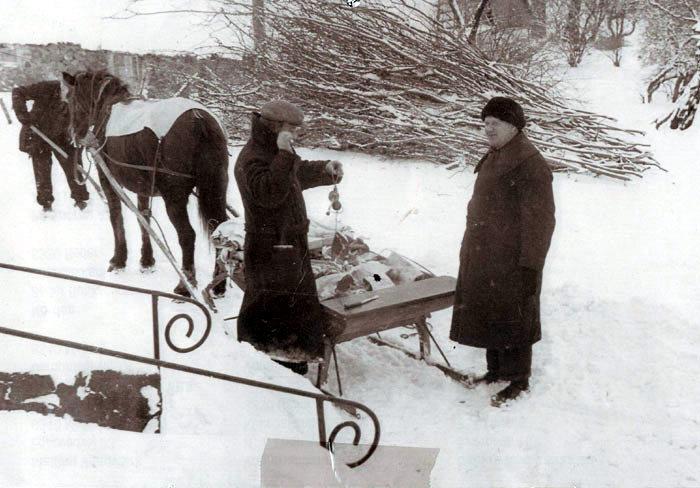 Januar Slagter Albert Weng, hvis forretning lå på Kirkebakken 22 (overfor Det gamle Mejeri) ses her i den hårde vinter, hvor han bringer varer ud til kunderne på hestetrukket slæde. Her vejer han kødet på sin bismervægt. Foto 1940-45