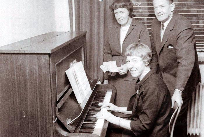 Det er Ester Jacobsen ved  klaveret, omsorgsleder Ester Gisselmann stående og formand for socialudvalget Elvin Hansen. Foto 1967